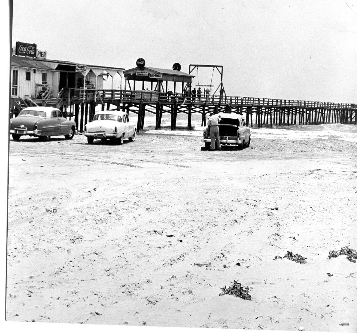 Classic automobiles roll up to a fishing pier in Port Aransas, May 1955.