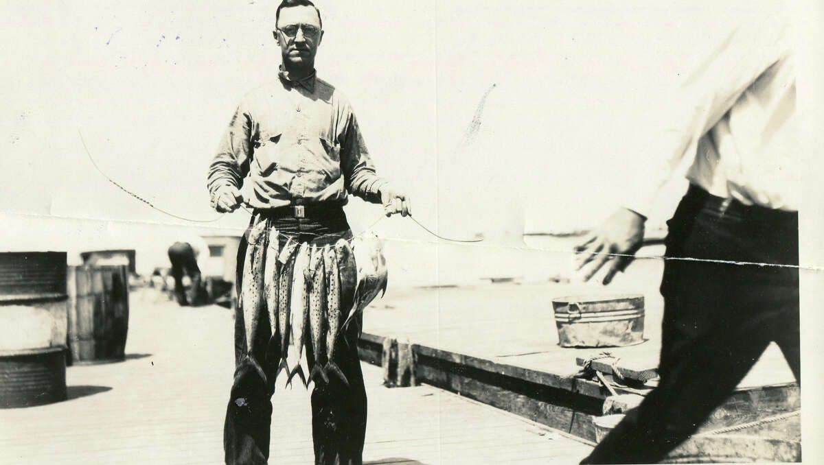 This man is caught with a successful string of fish, 1930.