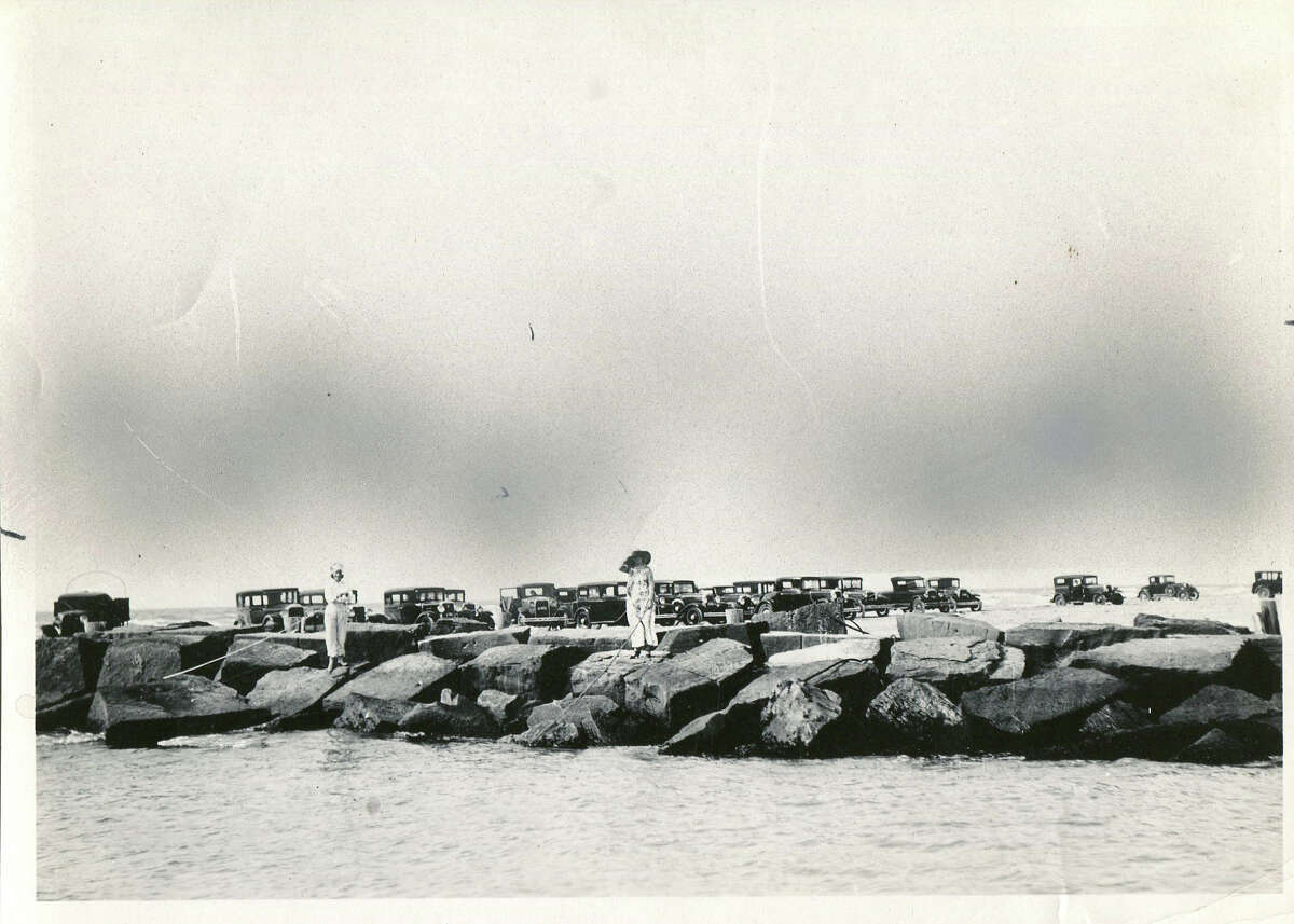 A line of old Model Ts are parked near a jetty where two women fish.