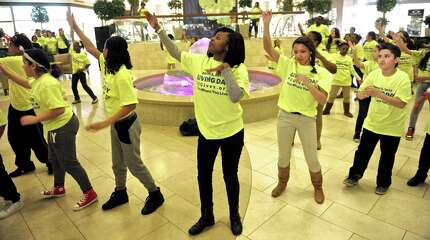 Dyshona Richards, of Bridgeport, center, leads a flash mob of 77 Bridgeport middle and high school students as they perform at the Danbury Fair Mall, Tuesday evening, to promote Fairfield County's Giving Day. The Giving Day's goal is to raise $1 million in 24 hours for 400 Fairfield County non-profit organizations. The students, part of Creative Youth Productions, from Bridgeport, performed an original song and dance number, on Tuesday, March 3, 2015, in Danbury, Conn.