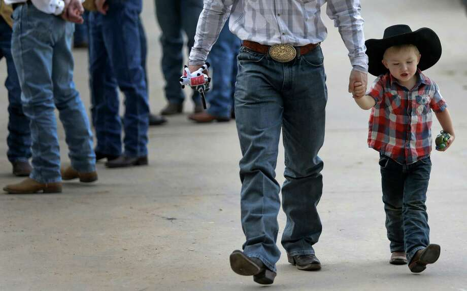 Dustin Flundra walks with his son, Ridge Flundra, 3, of Pincher Creek, Alberta, Canada at the Houston Livestock Show and Rodeo outside NRG Stadium Tuesday, March 3, 2015, in Houston. Dustin is a saddle bronc rider. Photo: Melissa Phillip, Houston Chronicle / © 2014  Houston Chronicle