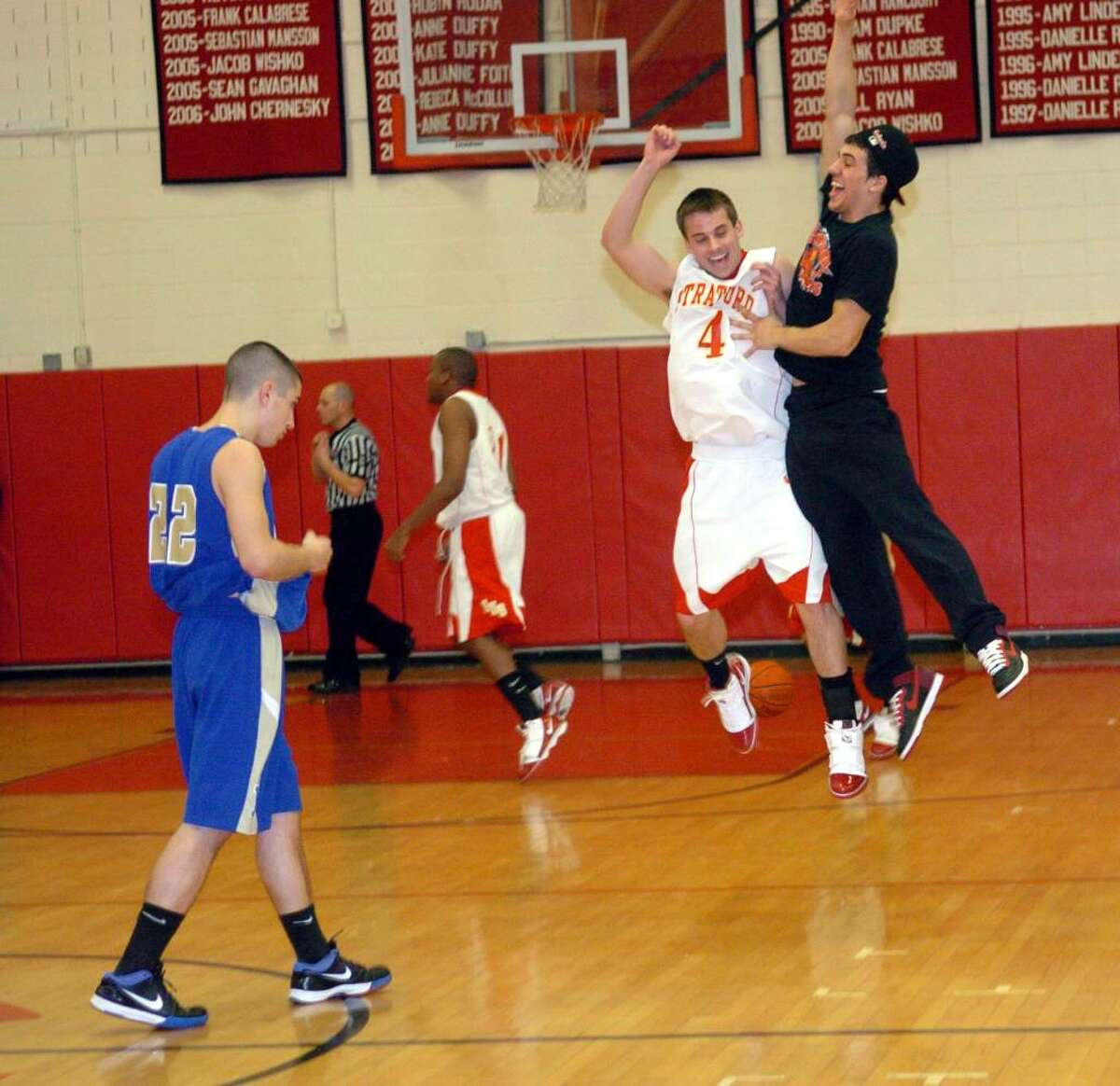 Stratford's #4 Jeff Miller leaps in the air with student Vinny Valente, after the team beat Newtown in SWC Championship action in Monroe on Thursday March 04, 2010.