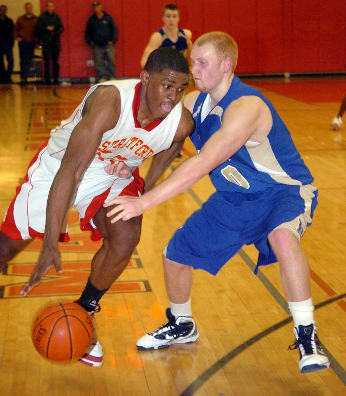 Stratford's #35 Brandon Sherrod, left, takes the ball around Newtown's #50 George Zaruba, during SWC Championship action in Monroe on Thursday March 04, 2010. Stratford went on to win 53-41.