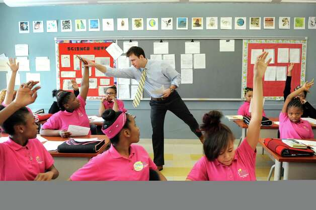 Science teacher Tom Joyce, center, high fives Za' Navid Cancer, 11, when she's selected to show her work in sixth-grade science class on Tuesday, March 3, 2015, at Brighter Choice Middle School for Girls in Albany, N.Y. (Cindy Schultz / Times Union) Photo: Cindy Schultz / 00030801A