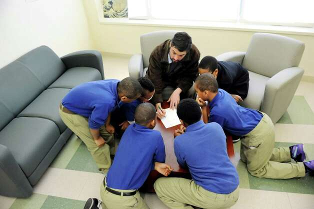 Math teacher Brian Rogers, center, goes over a new lesson on dividing decimals with his top students in fifth-grade math class on Tuesday, March 3, 2015, at Brighter Choice Middle School for Boys in Albany, N.Y. (Cindy Schultz / Times Union) Photo: Cindy Schultz / 00030801A