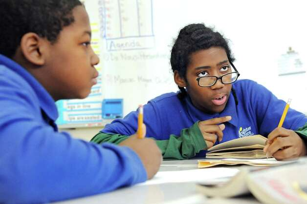 """Emir Crooks, 11, left, and Emmanuel Aviles, 12, dissect the book """"Maniac Magee"""" during their fifth-grade English Language Arts reading class on Tuesday, March 3, 2015, at Brighter Choice Middle School for Boys in Albany, N.Y. (Cindy Schultz / Times Union) Photo: Cindy Schultz / 00030801A"""