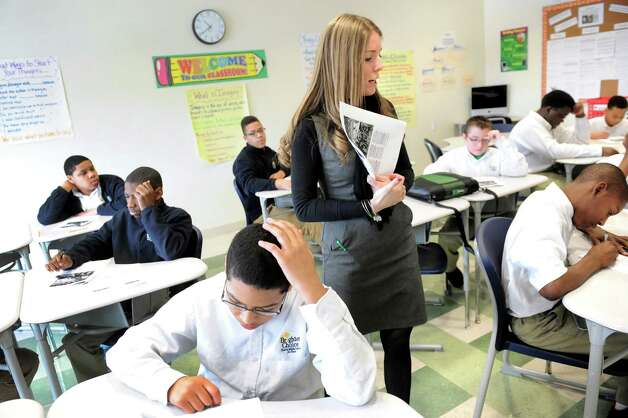 Teacher Arielle Buccella, center, works with her students in eighth-grade English Language Arts class on Tuesday, March 3, 2015, at Brighter Choice Middle School for Boys in Albany, N.Y. (Cindy Schultz / Times Union) Photo: Cindy Schultz / 00030801A