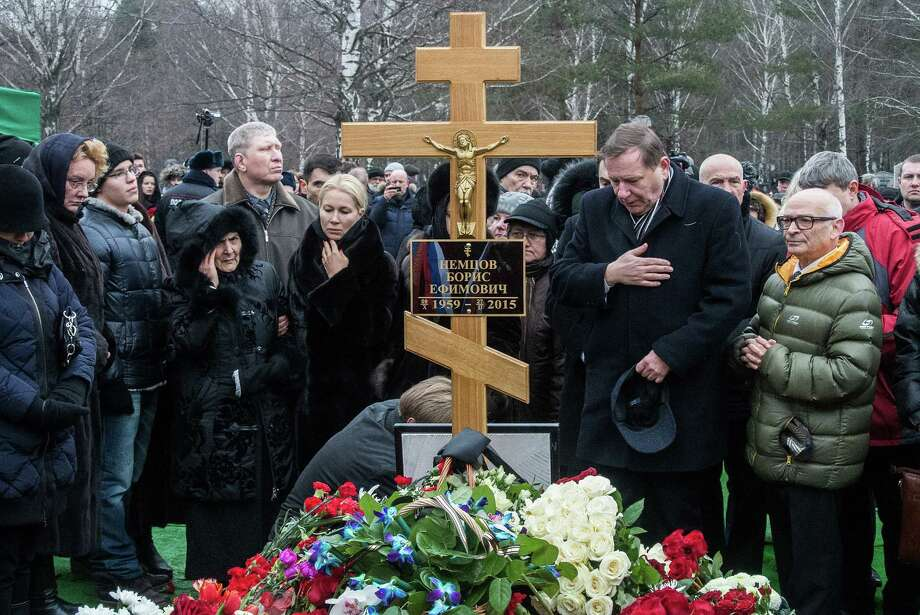 MOSCOW, RUSSIA - MARCH 03:   People place flowers near the cross at the grave of Russian opposition leader Boris Nemtsov at Troyekurovskoye Cemetary on March 3, 2015 in Moscow, Russia. Nemtsov was murdered on Bolshoi Moskvoretsky bridge near St. Basil cathedral just few steps from the Kremlin on February 27. Nemtsov, a fierce critic of President Vladimir Putin, was shot dead ahead of a major opposition rally this weekend. (Photo by Alexander Aksakov/Getty Images) Photo: Alexander Aksakov, Stringer / Getty Images / 2015 Getty Images