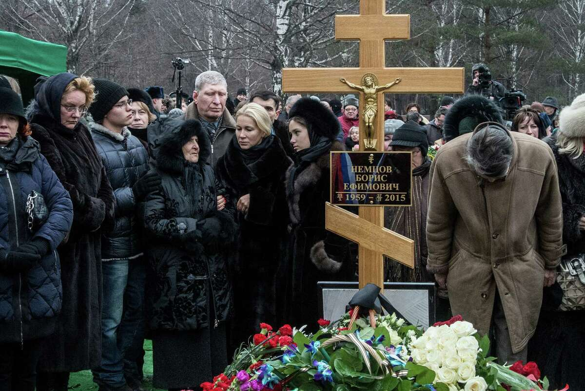 MOSCOW, RUSSIA - MARCH 03: People place flowers near the cross at the grave of Russian opposition leader Boris Nemtsov at Troyekurovskoye Cemetary on March 3, 2015 in Moscow, Russia. Nemtsov was murdered on Bolshoi Moskvoretsky bridge near St. Basil cathedral just few steps from the Kremlin on February 27. Nemtsov, a fierce critic of President Vladimir Putin, was shot dead ahead of a major opposition rally this weekend. (Photo by Alexander Aksakov/Getty Images)