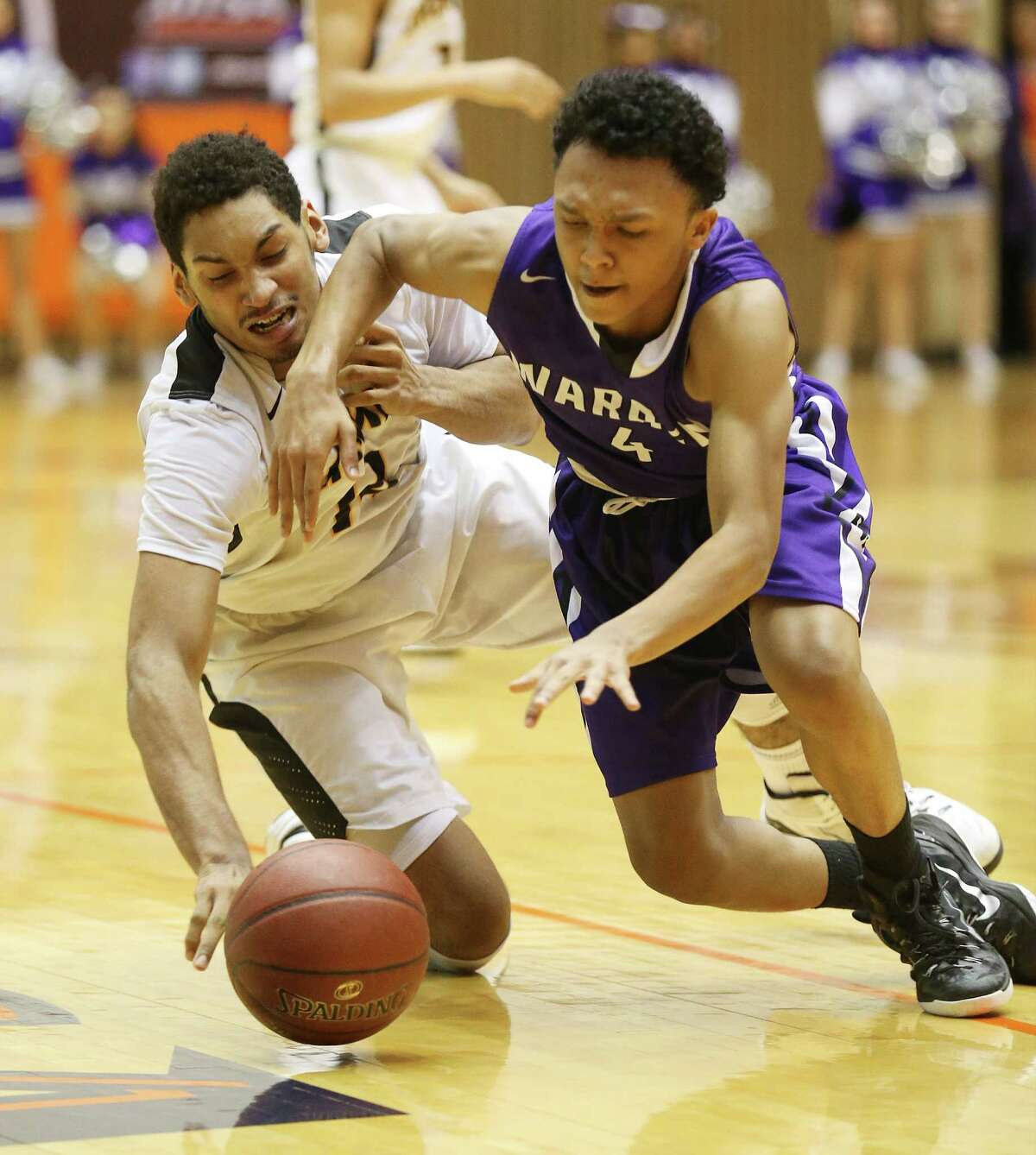 Brennan's Jordan Murphy (14) and Warren's Isaiah Thorne (4) compete for a loose ball in Region IV quarterfinals at UTSA on March 3, 2015.