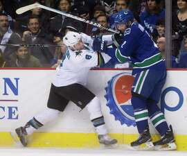 The Sharks' Joe Pavelski collides with Vancouver's Dan Hamhuis during the first period.