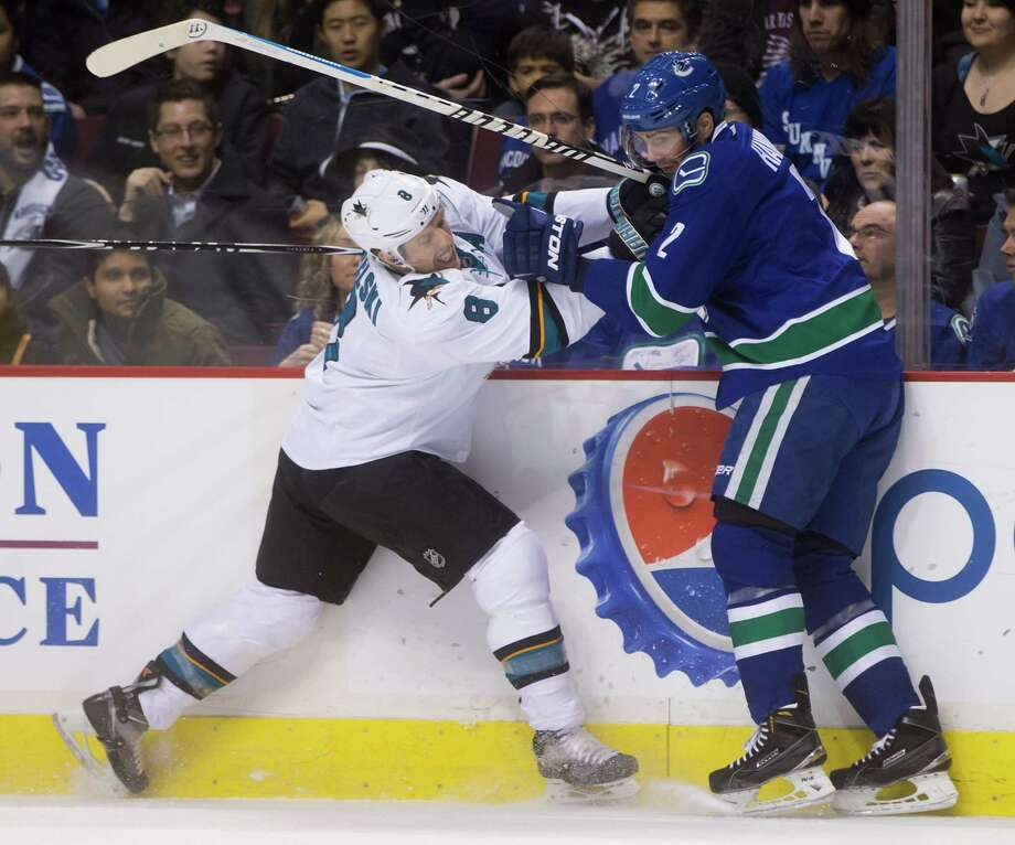 The Sharks' Joe Pavelski collides with Vancouver's Dan Hamhuis during the first period. Photo: DARRYL DYCK / Associated Press / The Canadian Press