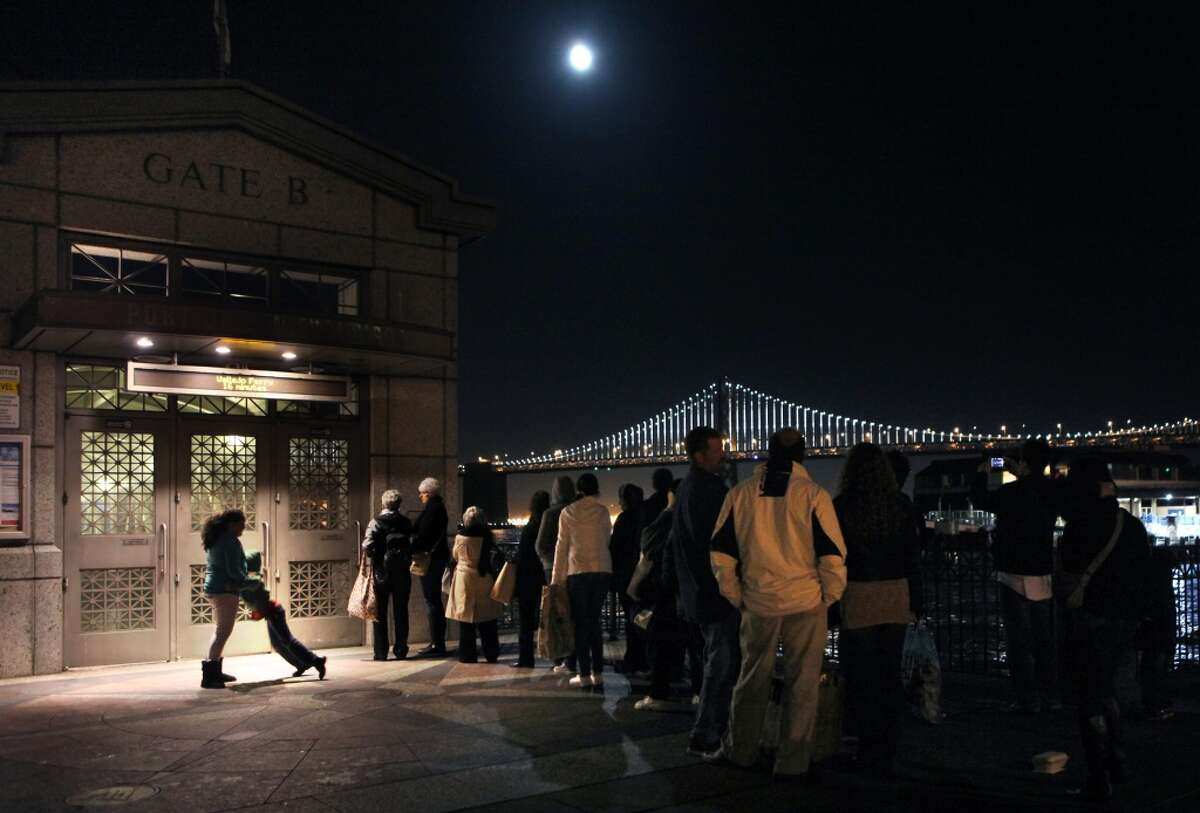 The Bay Lights seen from gate 5 of the Ferry Building as commuters wait for a ferry in San Francisco, California, on Friday, November 15, 2013. The Bay Bridge will host the light sculpture, designed by artist Leo Villareal until March of 2015.