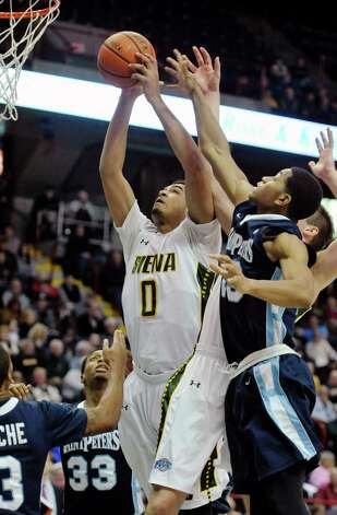 Javion Ogunyemi of Siena grabs an offensive rebound  during their game against Saint Peter's at the Times Union Center on Sunday, Jan. 25, 2014, in Albany, N.Y.    (Paul Buckowski / Times Union) Photo: Paul Buckowski / 00030241B