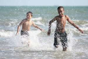 Children splash in the water as they race to the shore at Stewart Beach in Galveston.