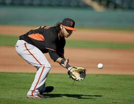 San Francisco Giants' Brandon Crawford (35) makes a play during spring training baseball practice Friday, Feb. 27, 2015, in Scottsdale, Ariz. (AP Photo/Darron Cummings)