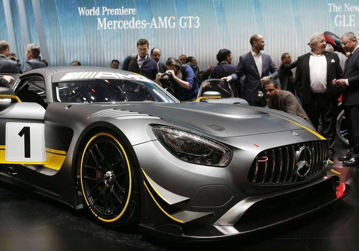 Journalists surround the new Mercedes-AMG GT3 on the first press day of the Geneva International Motor Show Tuesday, March 3, 2015 in Geneva, Switzerland. The show opens its doors to the public March 5 through March 15.