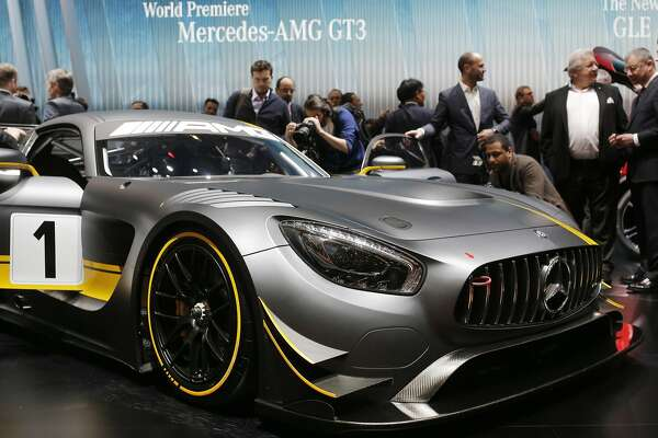 Journalists surround the new Mercedes-AMG GT3 on the first press day of the Geneva International Motor Show Tuesday, March 3, 2015 in Geneva, Switzerland. The show opens its doors to the public March 5 through March 15. (AP Photo/Laurent Cipriani)