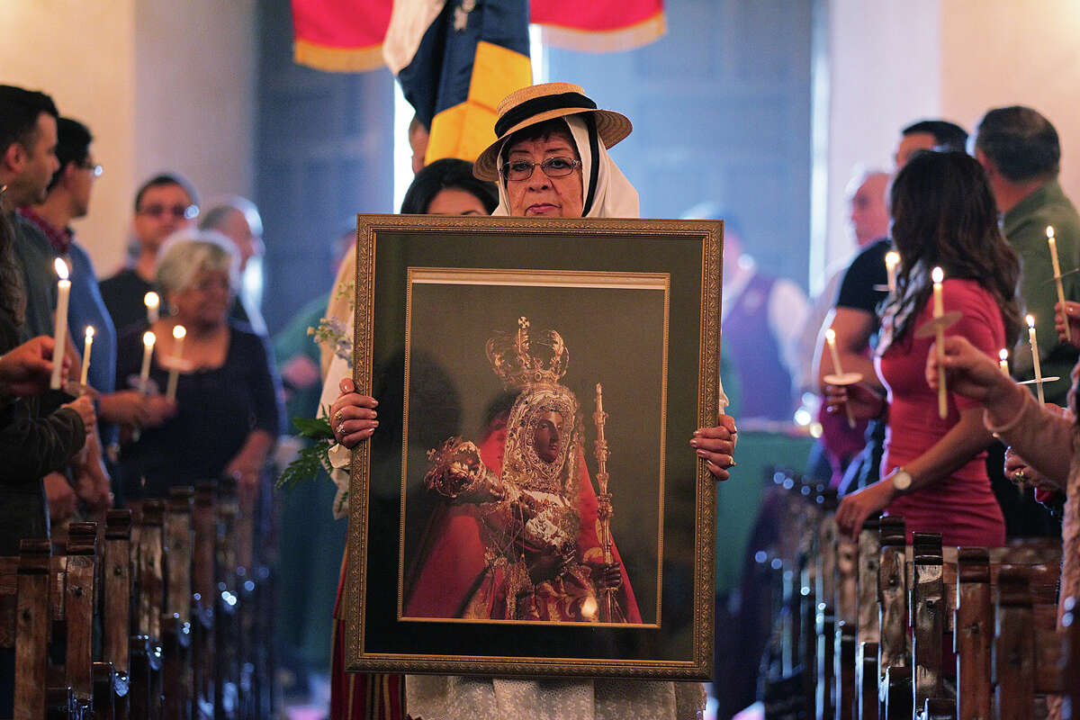 A portrait of Our Lady of Candelaria is carried by Socorro Morales to lead the procession as Canary Island Descendants Association of San Antonio members gather at Mission Concepcion in her honor, on Feb. 1.