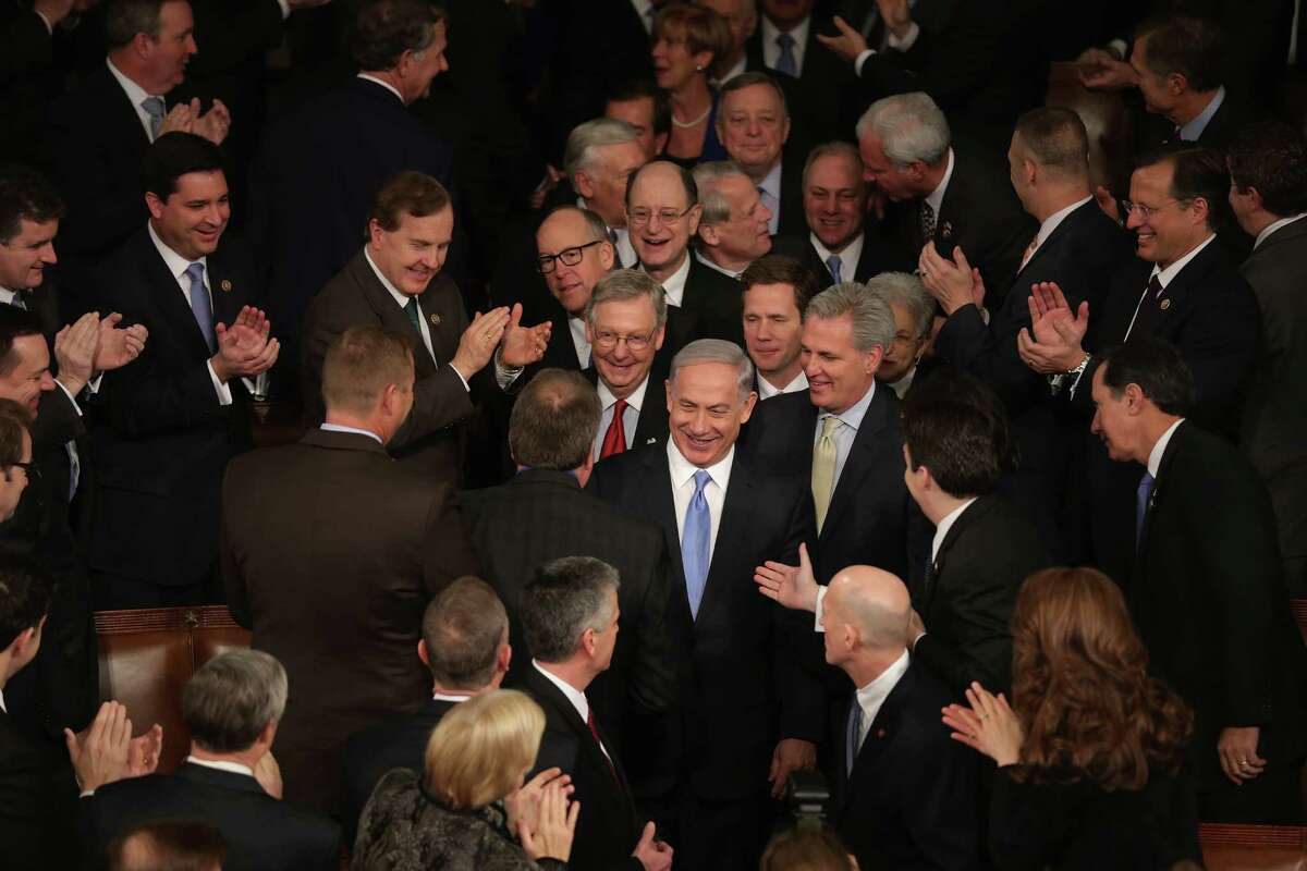 Israeli Prime Minister Benjamin Netanyahu (center) is greeted by members of Congress as he arrives to speak during a joint meeting of Congress on Tuesday.