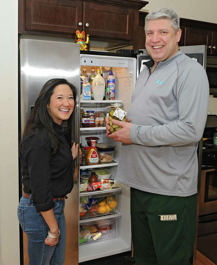 Michele and Jimmy Patsos stand next to their refrigerator in their home on Thursday, Feb. 26, 2015 in Albany, N.Y. Jimmy is holding one of his favorite things in the refrigerator, pickles from The Country Cottage. (Lori Van Buren / Times Union) Photo: Lori Van Buren / 00030723A