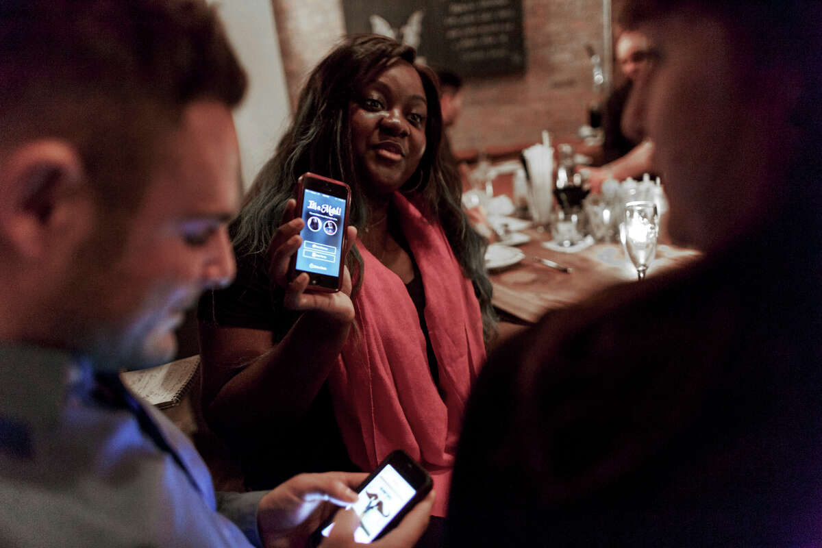 Patrons use Tinder, an online dating app, while at Bondurants, a bar in New York. It replaces profiles and algorithms with streams of photographs and very short biographies.