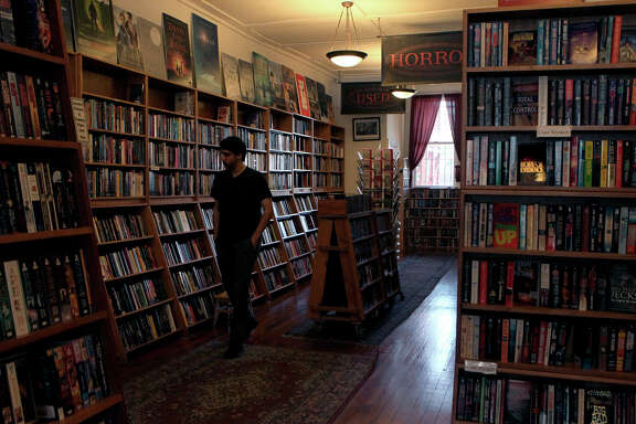 A customer glances over the wide selection of books at Borderlands bookstore in the Mission District, where the owner was on the brink of going out of business until his regular customers stepped up to help him out.