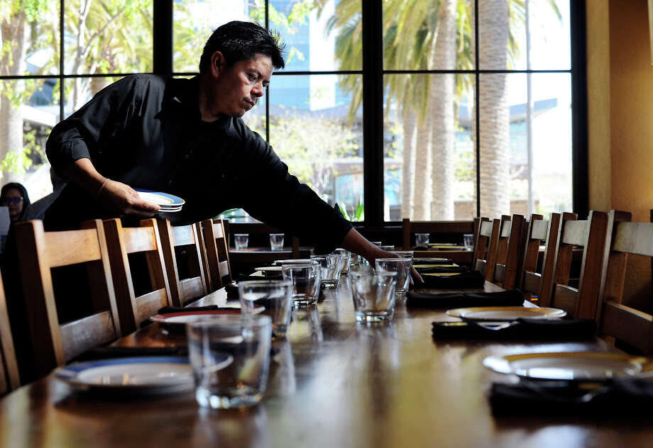 Andres Sanchez sets a table for lunch at Oakland's Bocanova, which has done away with traditional tipping. Photo: Michael Short / ONLINE_YES