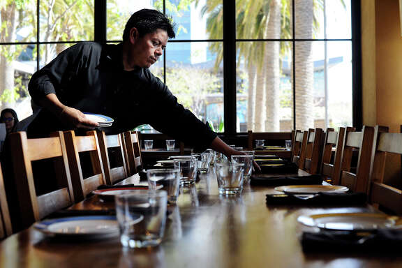 Andres Sanchez sets a table for lunch at Oakland's Bocanova, which has done away with traditional tipping.