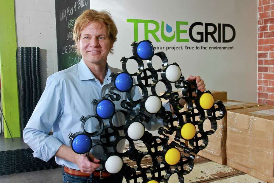 Barry Stiles, founder and CEO of Truegrid, holds a permeable paver with snap-in color parking markers. Photo: Gary Fountain, Freelance / Copyright 2015 by Gary Fountain