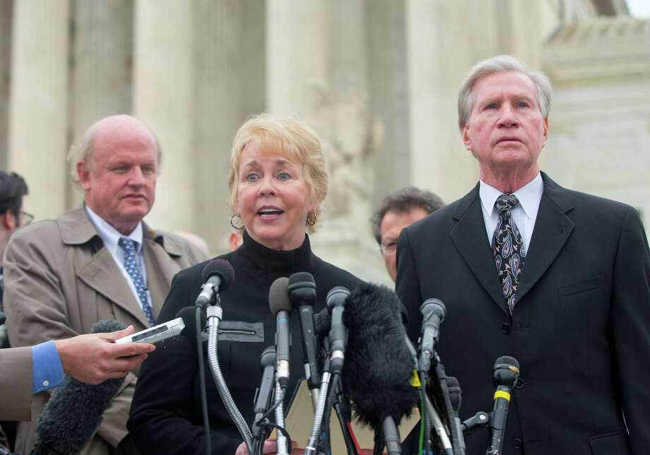 Pamela Hurst, left, wife of Douglas Hurst, right, plaintiff in King v. Burwell, speaks to reporters outside the Supreme Court in Washington, Wednesday, March 4, 2015, as Michael Carvin, left, lead attorney listens. The Supreme Court heard arguments in King v. Burwell, a major test of President Barack Obama's health overhaul which, if successful, could halt health care premium subsidies in all the states where the federal government runs the insurance marketplaces. (AP Photo/Pablo Martinez Monsivais) Photo: Pablo Martinez Monsivais, STF / AP