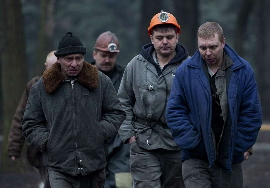 """Rescue workers head back from a Zasyadko coal mine in Donetsk, Ukraine, after a methane gas blast that left at least 24 dead. An anonymous spokesman said the chances of finding them alive were """"practically zero."""" Photo: JOHN MACDOUGALL, Staff / AFP"""