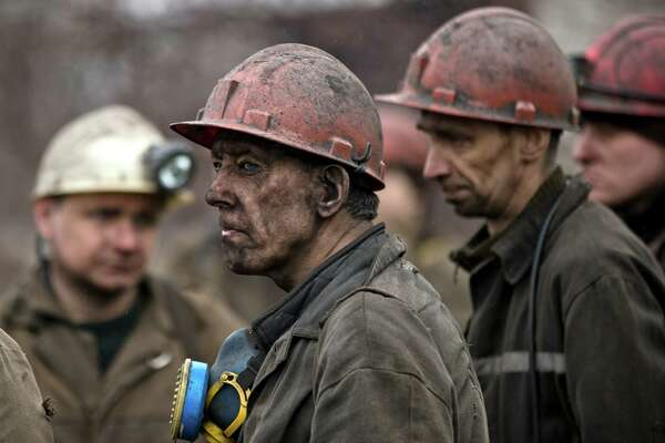 Ukrainian coal miners wait for a bus after returning to the surface of the Zasyadko mine in Donetsk, Ukraine, Wednesday, March 4, 2015. An explosion ripped through a coal mine before dawn Wednesday in war-torn eastern Ukraine, killing at least one miner and trapping more than 30 others underground, rebel and government officials said. One injured miner reported seeing five bodies. (AP Photo/Vadim Ghirda)