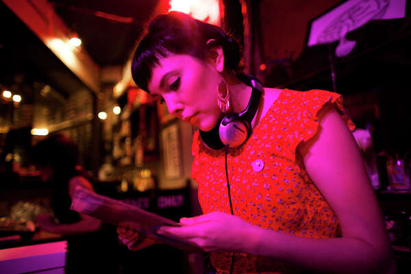 Amanda Reyna, a member of Chulita Vinyl Club, looks through at a record before performing a set Friday Feb. 13, 2015 at Hi-Tones club. Claudia Saenz formed Chulita Vinyl Club to bring women to the forefront of what is seen as a male-dominated scene. Since the group's launch in November, membership has steadily increased across Texas and has also gain international support.