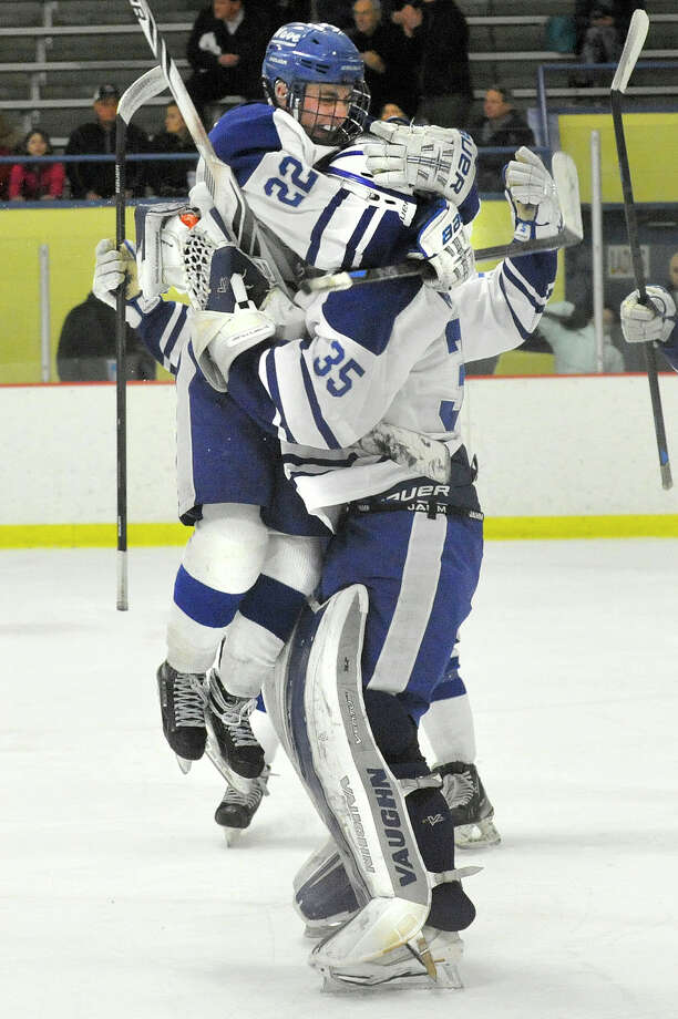 Darien's Jack Pardue, left, jumps into the arms of goalie Will Massie following the Blue Wave's 2-0 FCIAC semifinal defeat of New Canaan at Terry Conners Rink in Stamford, Conn., on Wednesday, March 4, 2015. Photo: Jason Rearick / Stamford Advocate