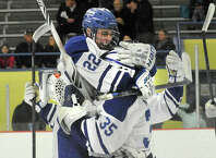 Darien's Jack Pardue, left, jumps into the arms of goalie Will Massie following the Blue Wave's 2-0 FCIAC semifinal defeat of New Canaan at Terry Conners Rink in Stamford, Conn., on Wednesday, March 4, 2015.