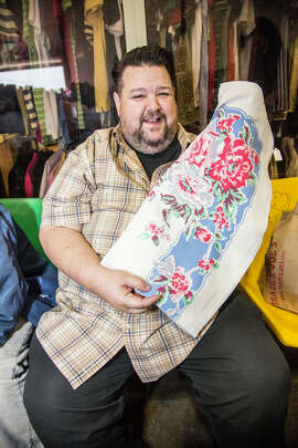 Chris March with vintage tablecloth at Oakland Museum White Elephant Sale.