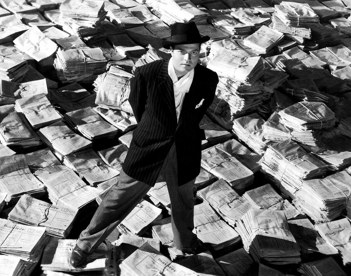 Orson Welles in CITIZEN KANE CITIZEN KANE, Orson Welles, 1941, astride stacks of newspaper