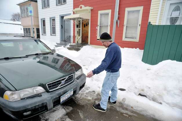 Eric Daus stands in the road about where he thinks the water pipe in frozen outside his mother's home on Fourth Ave., where he also lives, on Wednesday, March 4, 2015, in Troy, N.Y.  The water pipe leading into the home has frozen and the city says that it is the homeowners responsibility to hire someone to fix the problem.   Daus says that the pipe in frozen under the road and that the city should have to fix it. (Paul Buckowski / Times Union) Photo: PAUL BUCKOWSKI / 10030855A