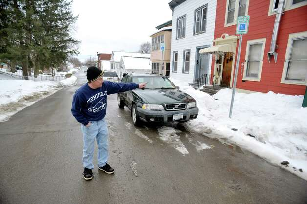 Eric Daus stands in the middle of the street outside his mother's home on Fourth Ave., where he also lives, on Wednesday, March 4, 2015, in Troy, N.Y. The water pipe leading into the home has frozen and the city says that it is the homeowners responsibility to hire someone to fix the problem.  Daus says that the pipe in frozen under the road and that the city should have to fix it. (Paul Buckowski / Times Union) Photo: PAUL BUCKOWSKI / 10030855A