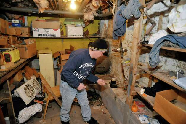 Eric Daus feeds a length of wire into the cut water line coming into the basement at his mother's home on Fourth Ave., where he also lives, on Wednesday, March 4, 2015, in Troy, N.Y.  The water pipe leading into the home has frozen and the city says that it is the homeowners responsibility to hire someone to fix the problem.  Daus says that using the wire he can tell that the blockage is under the road and that the city should fix it.  (Paul Buckowski / Times Union) Photo: PAUL BUCKOWSKI / 10030855A