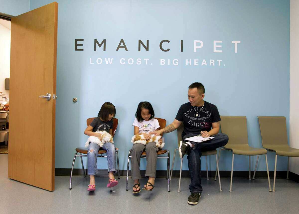 Ninh Nguyen, right, and his daughters Summer, left, 6, and Sydney, 8, wait in the lobby of Emancipet in Pflugerville with their two Shih Tzus, Cheech and Chong. The pups were among many others to get shots at the nonprofit clinic in 2013.