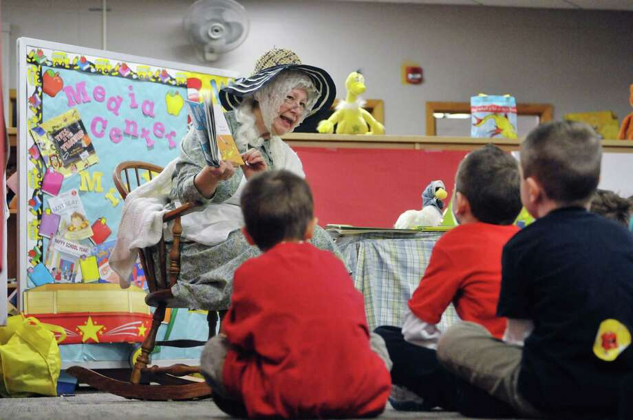 Former teacher Karen Schwenker, dressed as the character Mother Goose, reads to children during World Read Aloud Day at Turnpike Elementary School on Wednesday, March 4, 2015, in Lansingburgh, N.Y.  World Read Aloud Day is held to promote literacy world wide.  (Paul Buckowski / Times Union) Photo: PAUL BUCKOWSKI / 10030852A