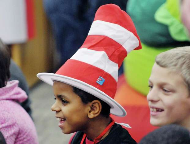 """Second grader Christopher Harrison wears a """"Cat in the Hat,"""" hat as he listens to a Dr. Seuss book being read to him and his classmates during World Read Aloud Day at Turnpike Elementary School on Wednesday, March 4, 2015, in Lansingburgh, N.Y.  World Read Aloud Day is held to promote literacy worldwide.  (Paul Buckowski / Times Union) Photo: PAUL BUCKOWSKI / 10030852A"""