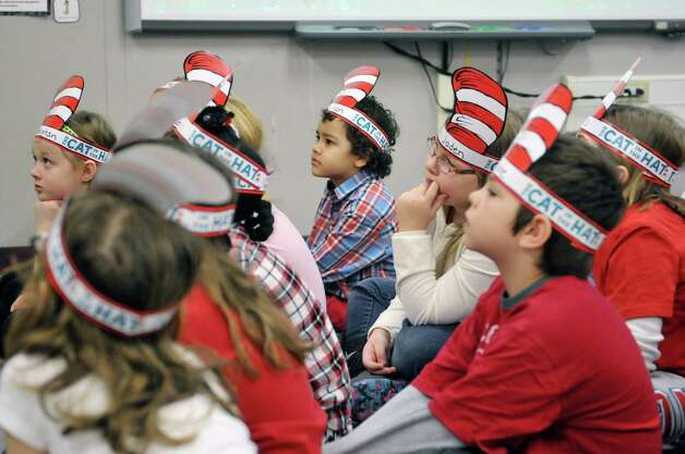 Second graders in Theresa McConnell's class listen as Marita Paredez, executive team leader of human resources at the East Greenbush Target store, reads a Dr. Seuss book to them during World Read Aloud Day at Turnpike Elementary School on Wednesday, March 4, 2015, in Lansingburgh, N.Y. (Paul Buckowski / Times Union) Photo: PAUL BUCKOWSKI / 10030852A