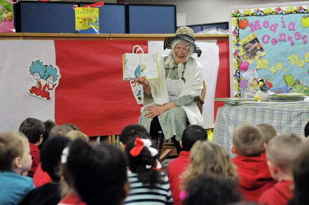 Former teacher Karen Schwenker, dressed as the character Mother Goose, reads to children during World Read Aloud Day at Turnpike Elementary School on Wednesday, March 4, 2015, in Lansingburgh, N.Y.  World Read Aloud Day is held to promote literacy worldwide.  (Paul Buckowski / Times Union) Photo: PAUL BUCKOWSKI / 10030852A