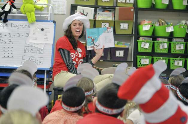 Marita Paredez, executive team leader of human resources at the East Greenbush Target store, reads a Dr. Seuss book to second graders in Theresa McConnell's class during World Read Aloud Day at Turnpike Elementary School on Wednesday, March 4, 2015, in Lansingburgh, N.Y.  McDonnell reached out to Target and seven employees came to the school to read to student on Wednesday.  The employees also brought craft supplies for the children. Target employees will be returning to the school throughout the year to work with the children.  (Paul Buckowski / Times Union) Photo: PAUL BUCKOWSKI / 10030852A