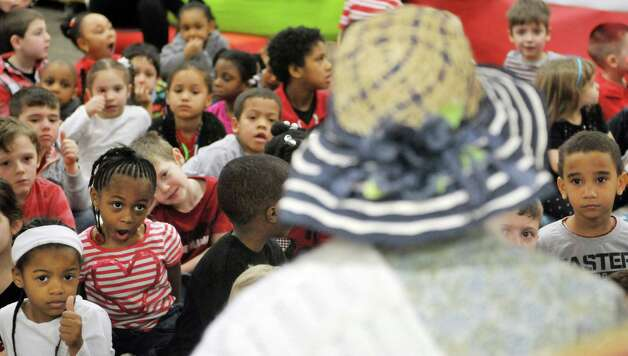 Former teacher Karen Schwenker, foreground, dressed as the character Mother Goose, reads to children during World Read Aloud Day at Turnpike Elementary School on Wednesday, March 4, 2015, in Lansingburgh, N.Y.   (Paul Buckowski / Times Union) Photo: PAUL BUCKOWSKI / 10030852A