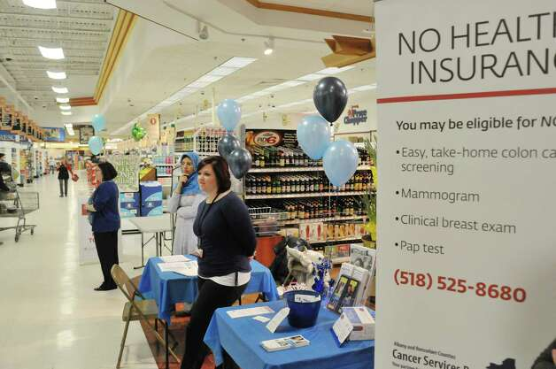 Christie Ray-Marchetti, left, with St. Peter's Health Partners, Dr. Asma Arif, a gastroenterologist from Troy, and Kelsey Sargood, with the Cancer Services Program of Albany & Rensselaer Counties, hold a colon cancer screening information event at the Brunswick Price Chopper on Wednesday, March 4, 2015, in Troy, N.Y.   (Paul Buckowski / Times Union) Photo: PAUL BUCKOWSKI / 10030853A