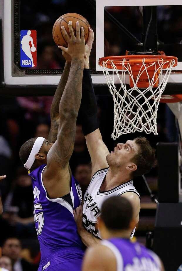 Spurs' Tiago Splitter blocks a shot by Sacramento Kings' DeMarcus Cousins at the AT&T Center on March 4, 2015. Photo: Kin Man Hui /San Antonio Express-News / ©2015 San Antonio Express-News